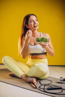 Женщина ест салат, изолированные на желтом фоне
