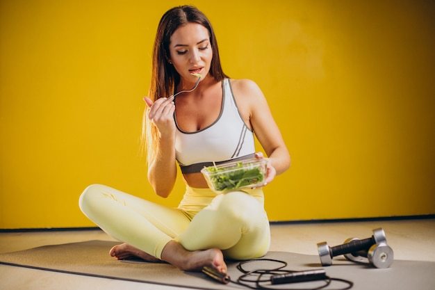 Woman eating salad isolated on yellow background
