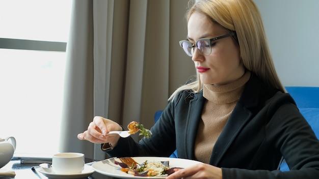 カフェ、コピースペースに座ってサラダを食べる女性