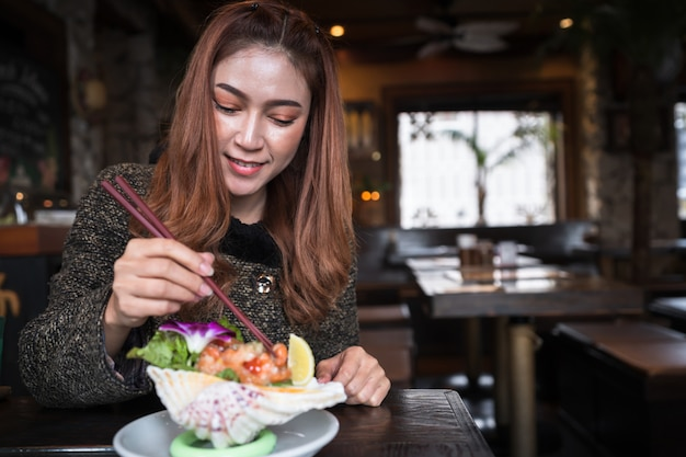 Woman eating salmon sashimi spicy salad in restaurant