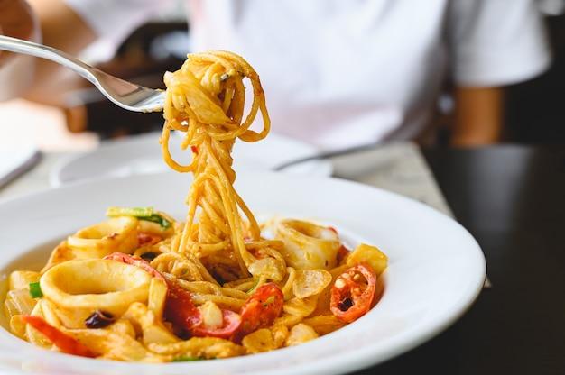 イタリア料理店でフォークとシーフードスパゲッティホワイトソースを食べる女性。食べ物と料理のコンセプト。