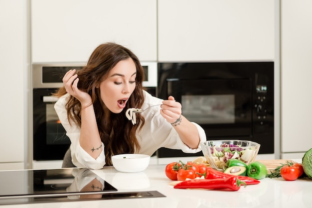 Woman eating soup from the spoon at the kitchen