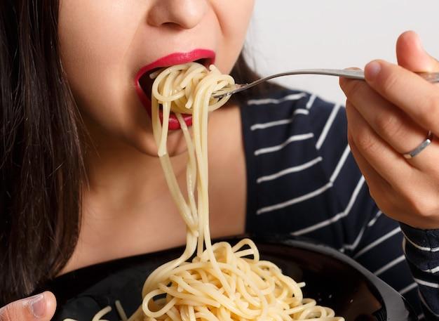 Женщина ест спагетти крупным планом.