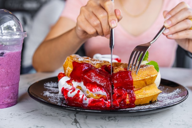 Woman eating strawberry waffles with knives and forks