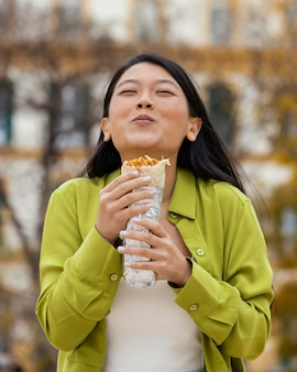 屋台の食べ物を食べる女性