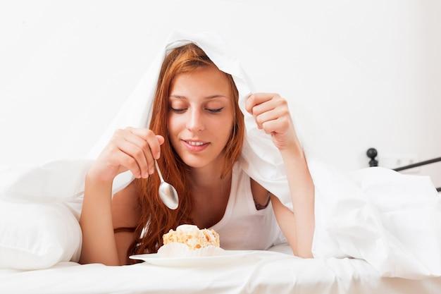 Женщина, едят сладкий торт в постели