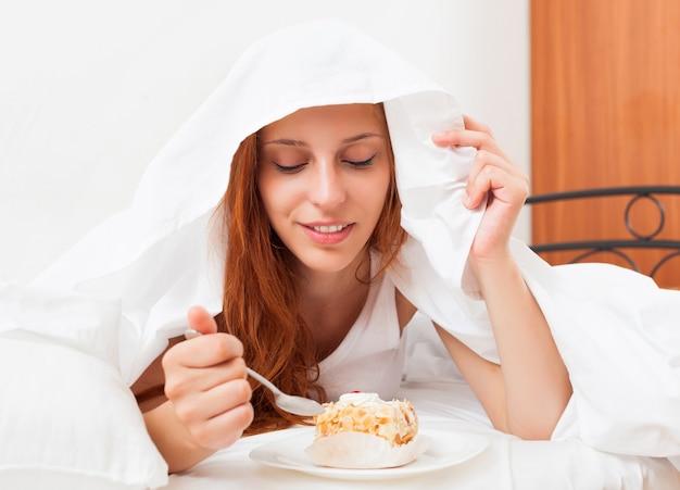 Женщина, едят сладкий торт под в постели