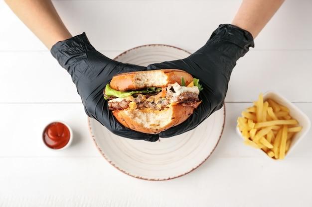 Женщина ест вкусный гамбургер за столом