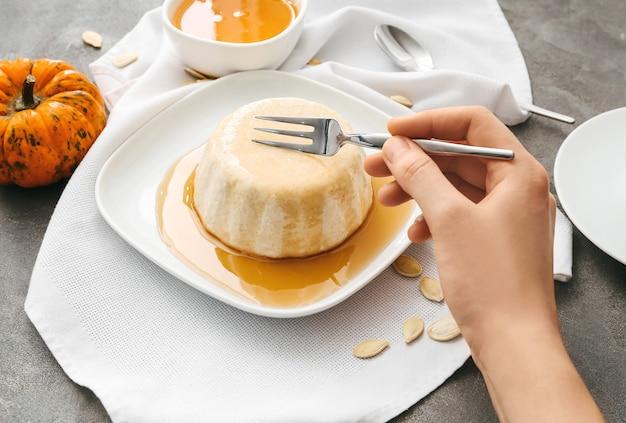 접시에서 맛있는 호박 푸딩을 먹는 여자