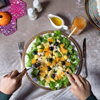 おいしいカボチャのサラダを食べる女性上面図