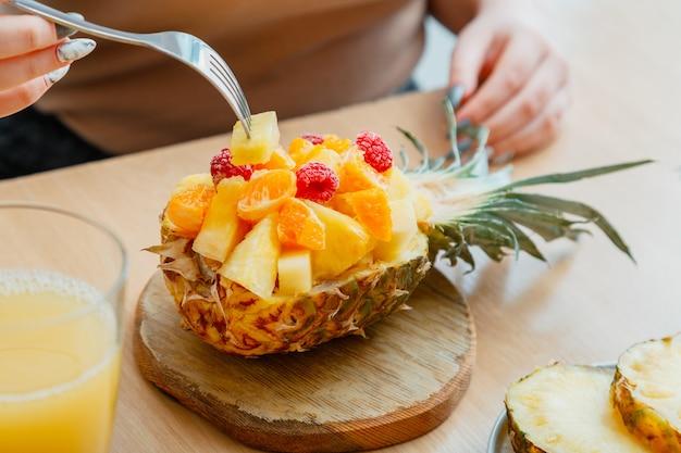 Woman eating tasty tropical fruit salad in half pineapple. berries raspberries pineapple tangerines oranges in dessert fruit salad in cafe. food fruit served in pineapple. high quality stock photo.