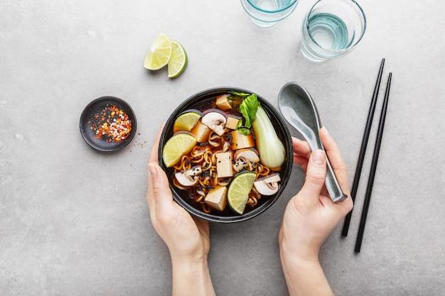 Woman eating tofu asian vegetarian soup in bowl