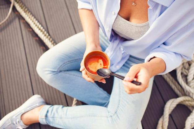 Женщина ест томатный суп в миску с ложкой