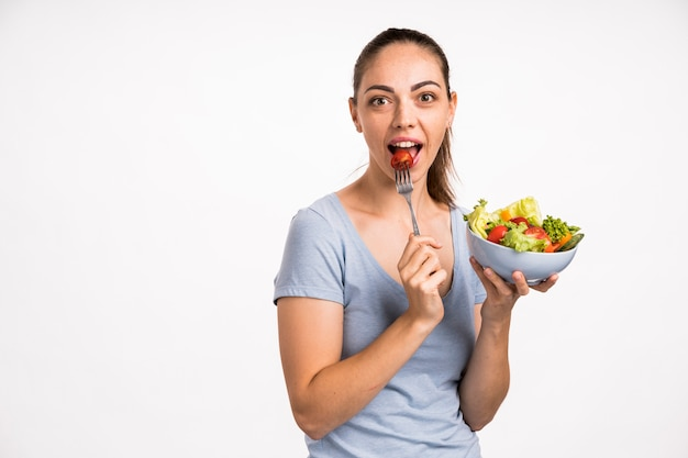 Woman eating a tomato with fork