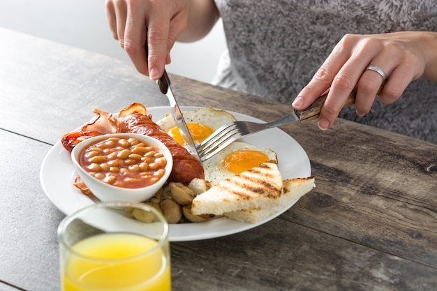 Woman eating a traditional english breakfast with fried eggs, sausages, beans, mushrooms, grilled tomatoes, bacon and orange juice on wooden table