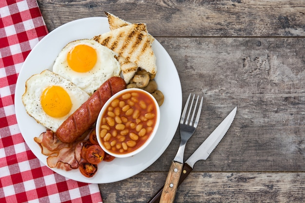 Woman eating a traditional english breakfast with fried eggs, sausages, beans, mushrooms, grilled tomatoes, bacon on wooden table