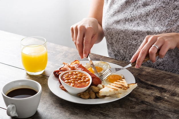Woman eating traditional full english breakfast with fried eggs, sausages, beans, mushrooms, grilled tomatoes and bacon on white wooden surface