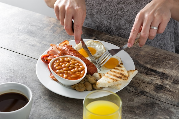 Woman eating traditional full english breakfast with fried eggs, sausages, beans, mushrooms, grilled tomatoes and bacon on wooden surface