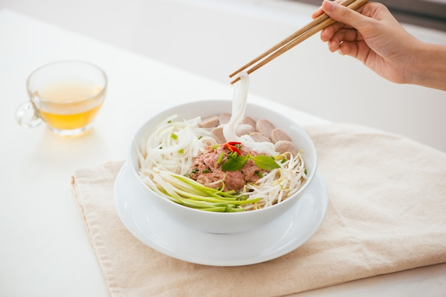 Woman eating traditional vietnamese pho noodle using chopsticks.