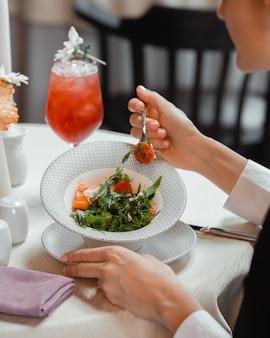 Женщина ест овощной салат с помидорами, болгарским перцем, укропом и рукколой