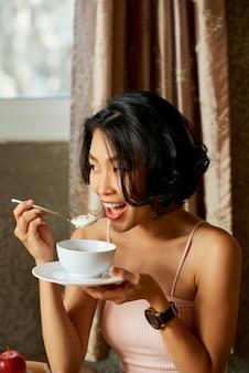 Женщина ест йогурт с мюслом