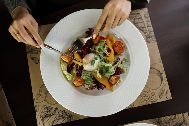 女性はレストランで新鮮な野菜とグリーンサラダの葉、新鮮な黄ピーマンと魚のかけらとポーチドエッグのサラダを食べます。上面図のクローズアップ。健康的な朝食