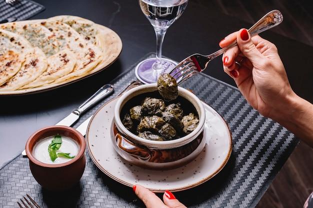 アゼルバイジャンのブドウの葉を食べる女性、ドルマとヨーグルトを添えて