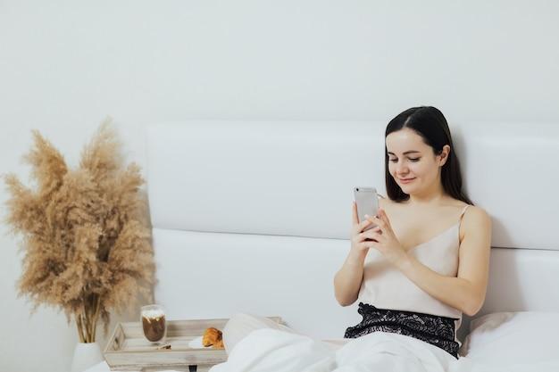 女性はベッドで朝食を食べ、電話を調べます