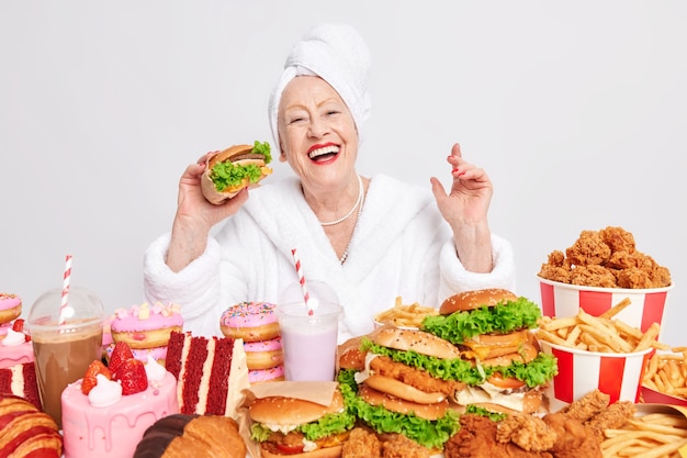 Woman eats delicious appetizing hamburger prefers eating fast food surrounded by variety of tasty high calorie products dressed in casual domestic clothes on white