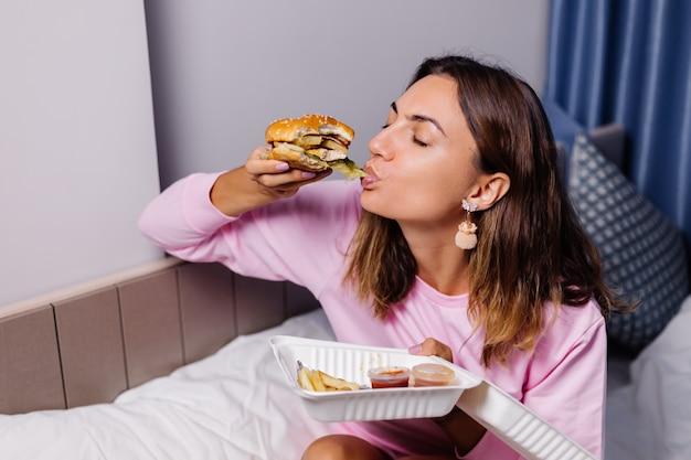 女性は家でハンバーガーを食べる