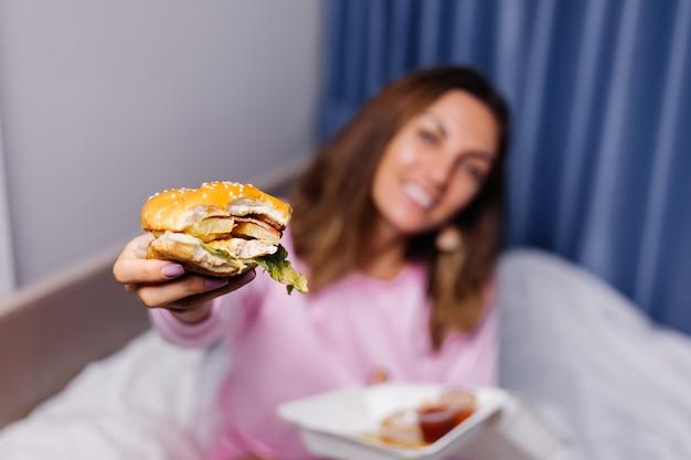 La donna mangia l'hamburger a casa