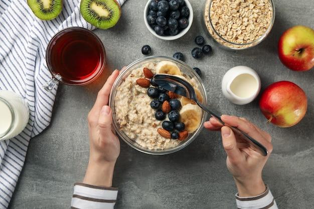 Woman eats oatmeal porridge. composition with oatmeal on gray