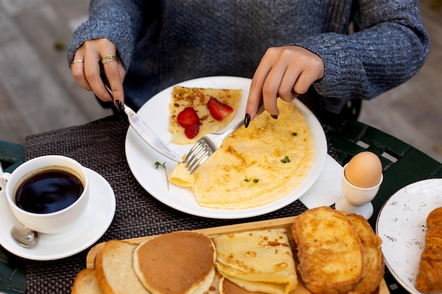 Woman eats omelet and crepe with strawberry