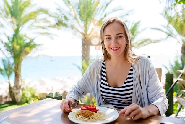 女性は海を背景にパスタを食べる