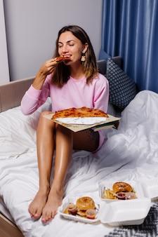 Woman eats pizza at home
