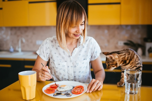 Woman eats at the table while bengla cat stands behind her