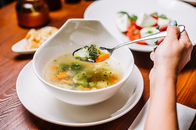 Женщина ест овощной суп с брокколи, морковью, сельдереем и картофелем