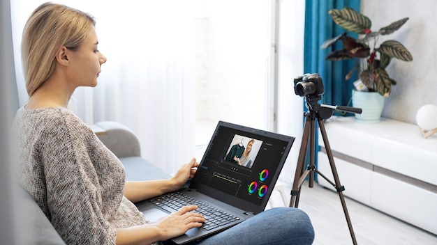Woman editing video on laptop computer for her vlog. woman working on laptop at home