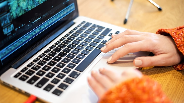 彼女のラップトップでビデオを編集している女性。テーブルの上のマイク。家で働く