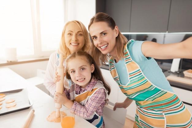 A woman, an elderly woman and a little girl make selfi.