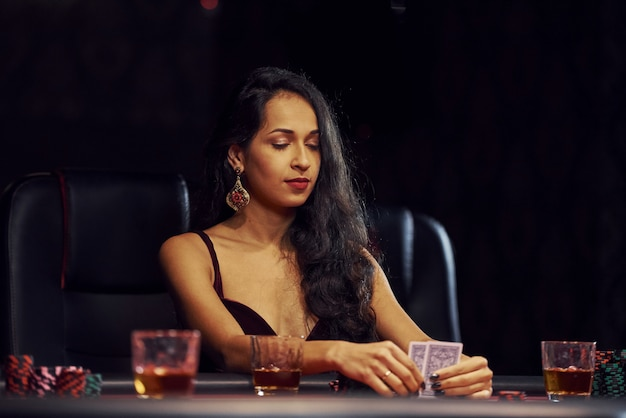 Woman in elegant clothes sits in cassino by table and plays poker game