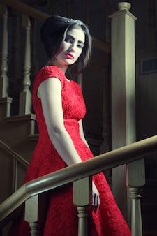 Woman in elegant dress posing on stairs