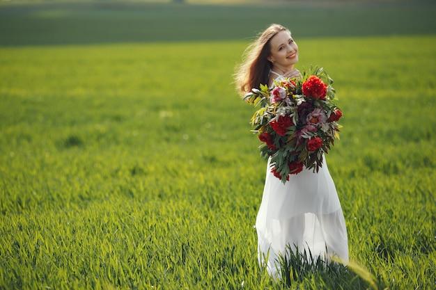 Donna in abito elegante in piedi in un campo estivo