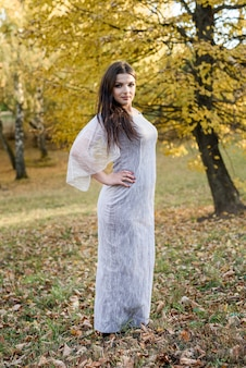Woman in elegant evening dress posing in autumn park. sunlights on trees in yellow colours