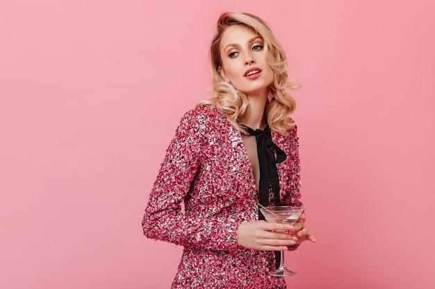 Donna in abito rosa elegante in posa con un bicchiere di champagne sulla parete isolata