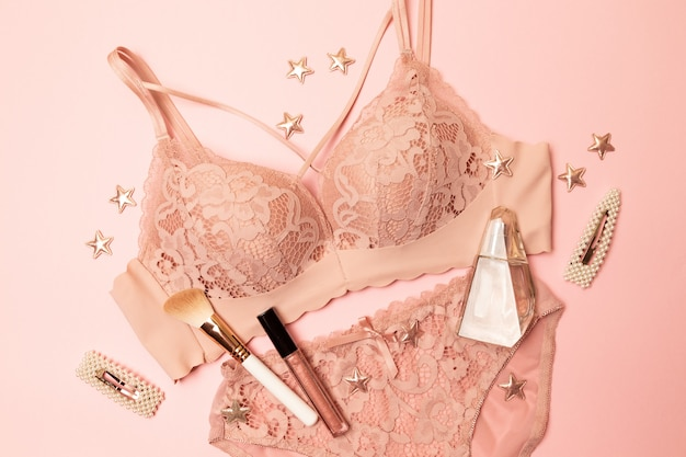 Woman elegant pink lace bra and panties, jewelry. stylish lingerie flat lay.