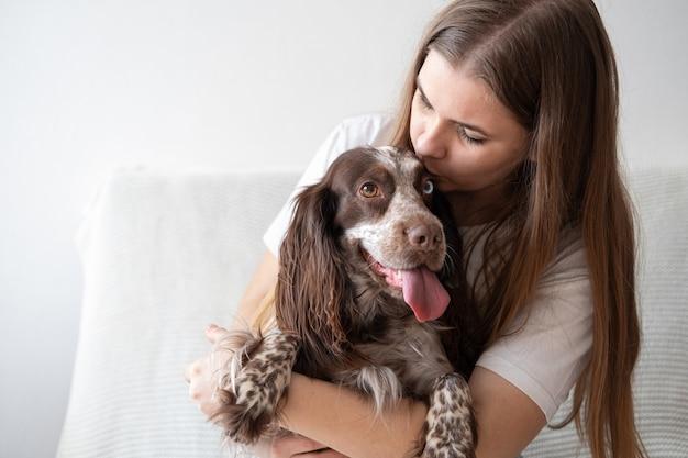 Женщина обнимает поцелуй русского спаниеля собака шоколадный мерль разных цветов глаза. концепция ухода за домашними животными.