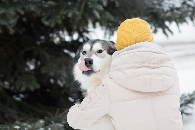 冬の森でアラスカンマラミュートを抱きしめる女性。閉じる。犬。