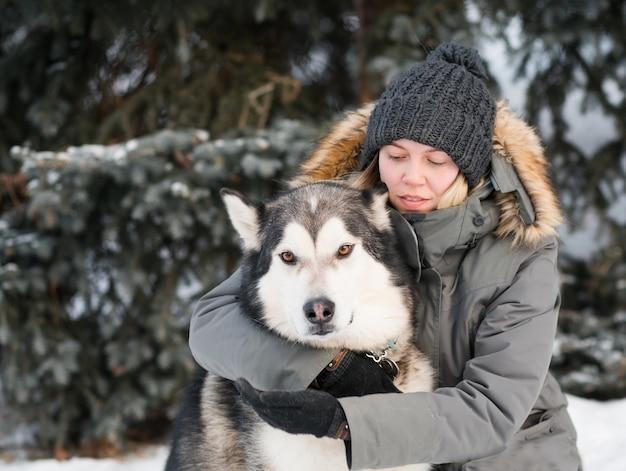 冬の森でアラスカンマラミュートを抱きしめる女性