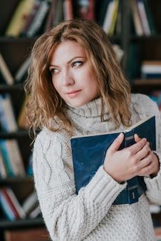女性が本を抱き、遠くを見ている